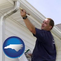 north-carolina map icon and a painting contractor brushing paint on an aluminum leader